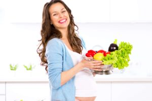 Pregnant young woman cooking vegetables. Healthy food
