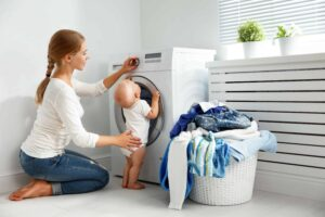 mother housewife with baby engaged in laundry fold clothes into washing machine